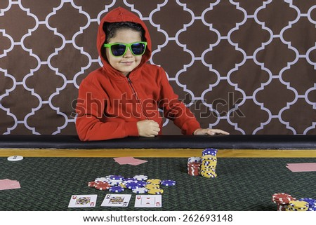 A young boy sitting at a poker table with a hoodie and sunglasses gambling playing cards with a brown background - stock photo