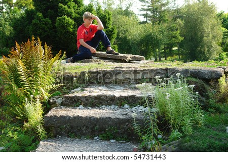 A young boy sitting on a stone - stock photo