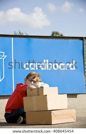 A young boy sitting with cardboard boxes in a recycling centre - stock photo
