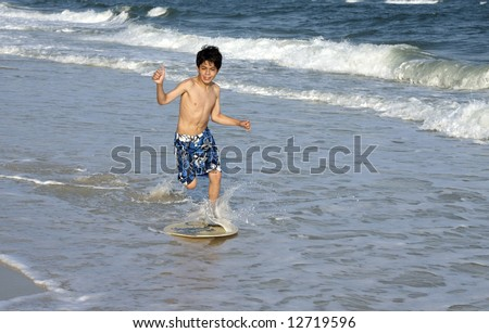 A young boy skimboarding. - stock photo