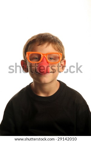 a young boy smiles while wearing funny clown nose glasses isolated on white - stock photo