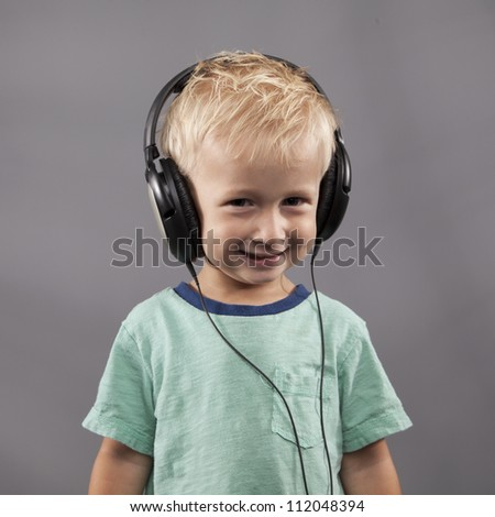 A young boy smiles with headphones on his head.