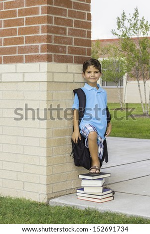 A young boy standing in front of a school with his foot on a stack of books.