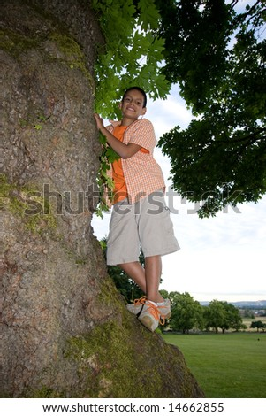 A young boy, standing on a tree, smiles for the camera. - vertically framed