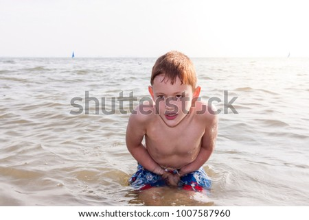 A young boy standing waist deep and shivering in the sea