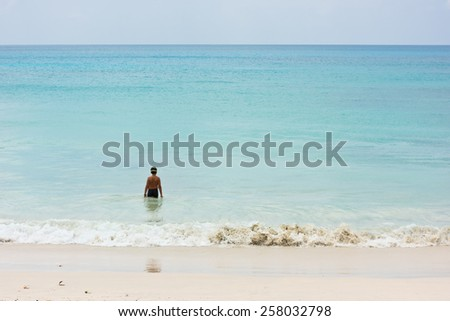 A young boy stands at shore and going to swim in the ocean. Back view, unrecognizable person - stock photo
