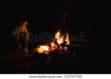 a young boy staring into a camp fire at night - stock photo