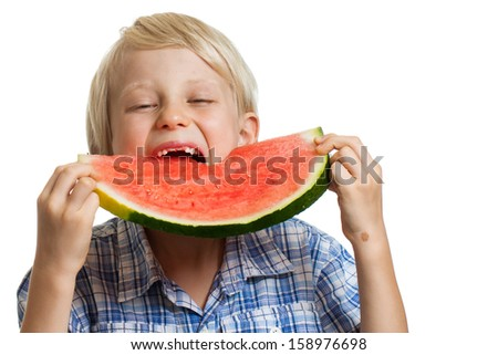 A young boy taking big bite of juicy slice of watermelon. Isolated on white.