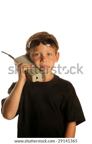 a young boy talks on a old 1980s era Brick Cell phone isolated on white - stock photo