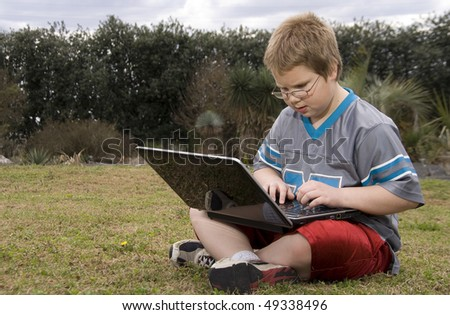 A young boy using a laptop computer - stock photo