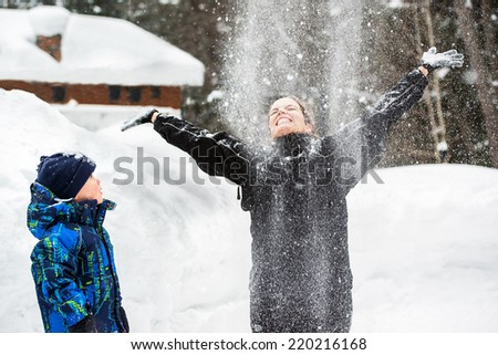 A young boy watches his mother throwing snow up in the air smiling with her arms out as it falls on her face.  - stock photo