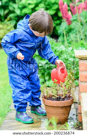 A young boy watering a plant in a pot - stock photo