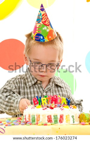 A young boy wearing a party hat decorates a birthday cake.