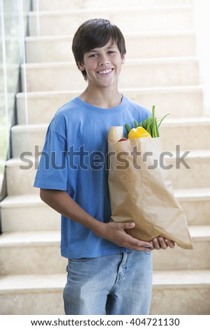 A young boy with a bag of shopping - stock photo