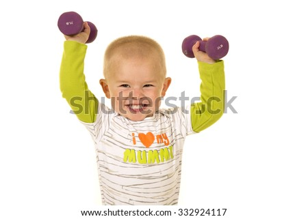 A young boy with a big smile, lifting up his weights.