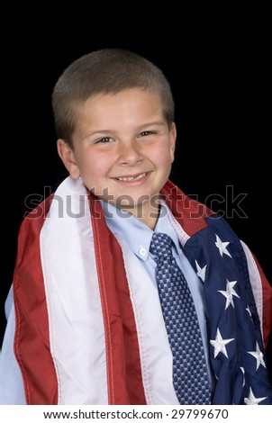 A young boy with a dress shirt and necktie has an American flag draped around his shoulders showing his patriotism. - stock photo