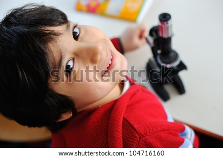 A young boy with a miscroscope - stock photo