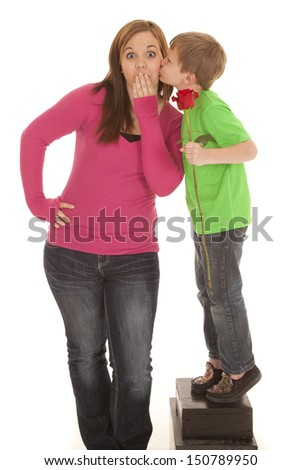 A young boy with a rose gives a girl a kiss on the cheek.