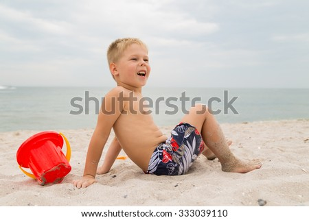 A young boy with bright bucket for sand on the beach. The boy spends a fun time for the molding of sand figures. Photo for children's magazines, websites and posters.
