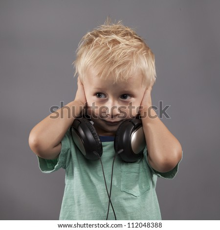 A young boy with headphones around his neck holds his hands over his ears. - stock photo