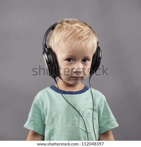 A young boy with headphones stares seriously in the camera.