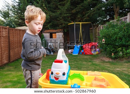 A young British caucasian boy with blond hair playing outside in a garden with a water table