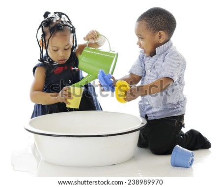 A young brother and sister having fun playing in a tub full of water and water toys.  On a white background.