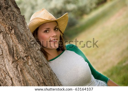 A young brunette in straw cowboy hat.  Narrow depth of field focusing on woman.