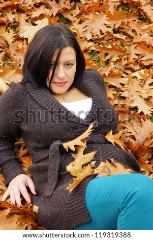A young brunette lying between many autumn leaves
