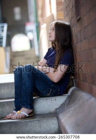 A young brunette teen girl in a alley looking contemplative and alone - stock photo