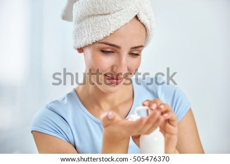 A young brunette woman with a towel wrapped round her head  putting moisturizer onto her hand