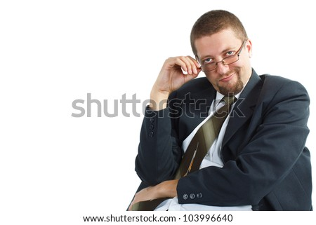 A young busimessman with glasses, suit and tie, looking into the camera with a funny, bossy expression, holding his glasses with one hand, sitting - isolated on white - stock photo