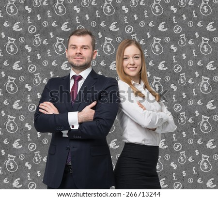 A young business couple are standing over the concrete money background.