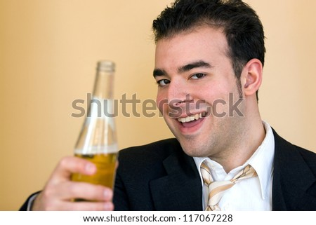 A young business man offering a beer after hours. Benjamin Franklin said that Beer is living proof that God loves us and wants us to be happy. - stock photo