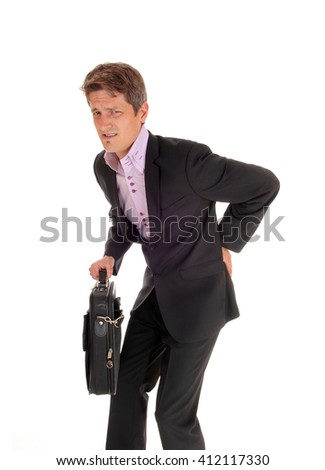 A young business man walking in a suit, holding his back 