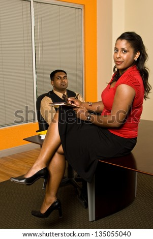 A young business professional with a cigar in his mouth is checking out his secretary's legs as she takes notes. - stock photo