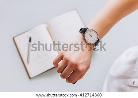 A young business woman checks time on her classic watch, she thinks about time management and corrects schedule in her diary - stock photo
