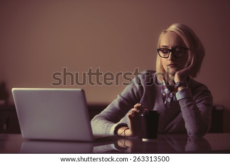 a young business woman is feeling tired at night in front of her laptop - stock photo