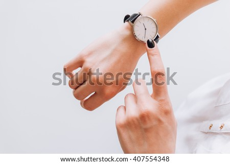 A young business woman is late on time, she shows the deadline on her classic watch - stock photo