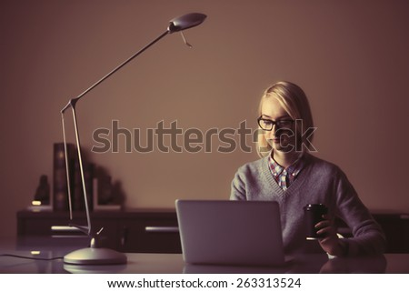 a young business woman is working in front of her laptop at night - stock photo