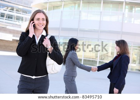 A  young business woman on the phone with coworkers shaking hands at office building