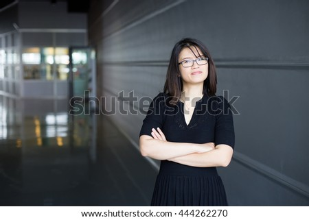 A young business woman smiling on a dark blurred background