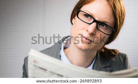 A young business woman wearing glasses holds a newspaper and looks to her side.