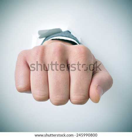 a young businessman breaks through a wall with his fist - stock photo