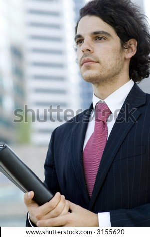 A young businessman holding document folder standing outside