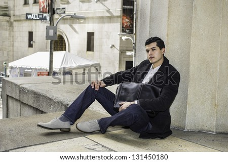 A young businessman hugging a bag  is sitting on the floor and take a break. There is a Wall Street sign on the background. - stock photo