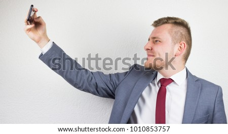 A young businessman in a suit, using a front camera of a mobile phone, a smile, a white background, a studio