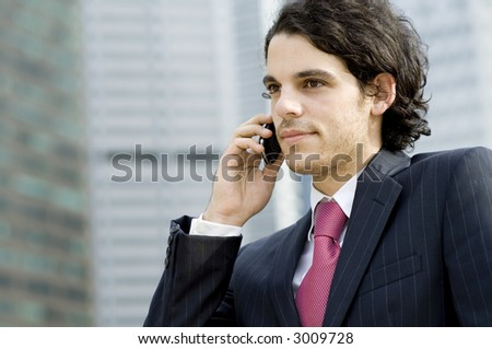 A young businessman in the city using a mobile phone outside (shallow depth of field used)