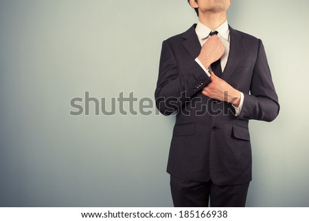 A young businessman is adjusting his tie - stock photo