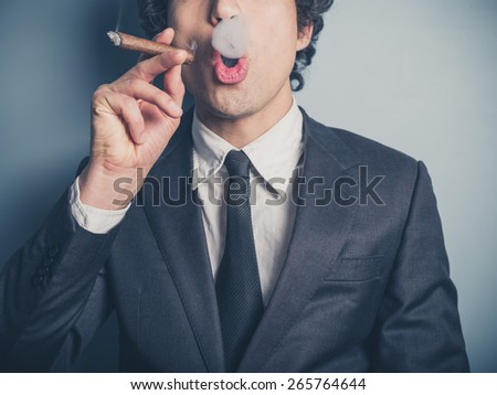A young businessman is smoking a cigar and is blowing smoke rings - stock photo